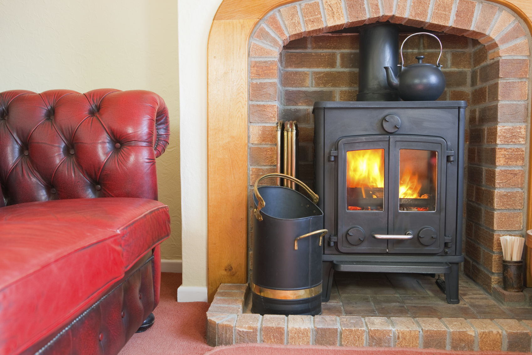 A hearth with a woodburning stove ablaze with logs and a Chesterfield settee.